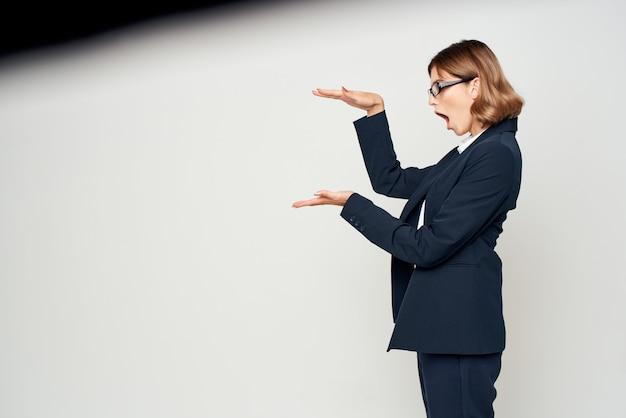 Mulher de terno gesticulando com a mão.
