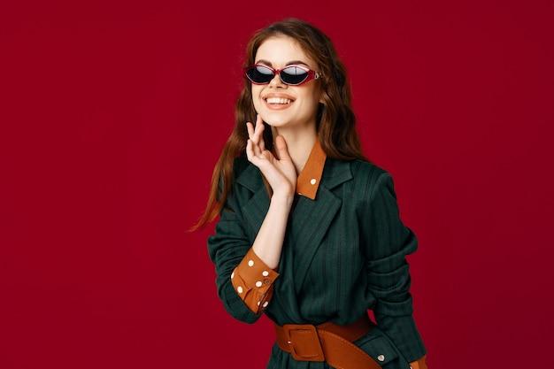 Mulher de terno gesticulando com as mãos, óculos de sol, fundo vermelho luxuoso
