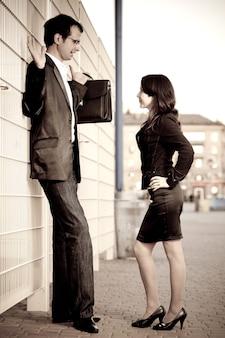 Mulher de terno preto pressionado homem de óculos com pasta para cercar na rua