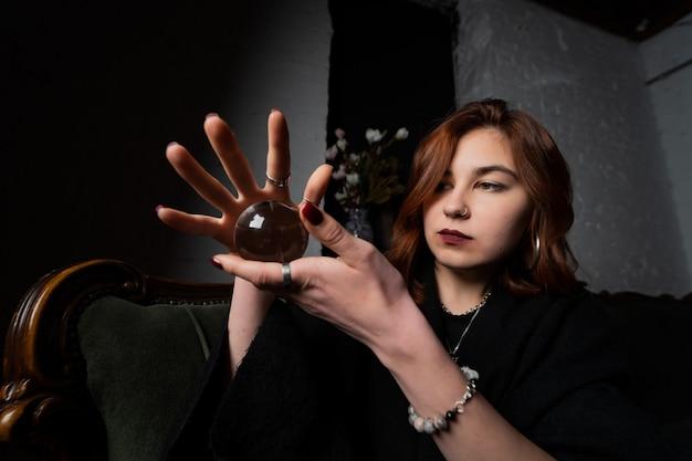 Mulher de terno preto segurando uma bola de cristal nas mãos