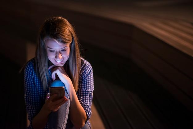 Mulher de texto. closeup jovem feliz sorrindo alegre mulher linda olhando telefone celular lendo enviando sms isolado parque paisagem urbana de fundo ao ar livre. expressão do rosto positivo emoção humana