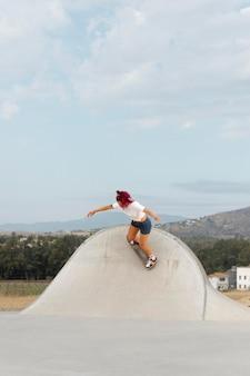Mulher de tiro certeiro fazendo manobras com o skate