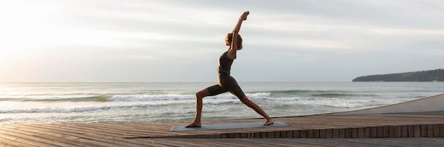 Mulher de tiro certeiro fazendo pose de guerreiro na praia
