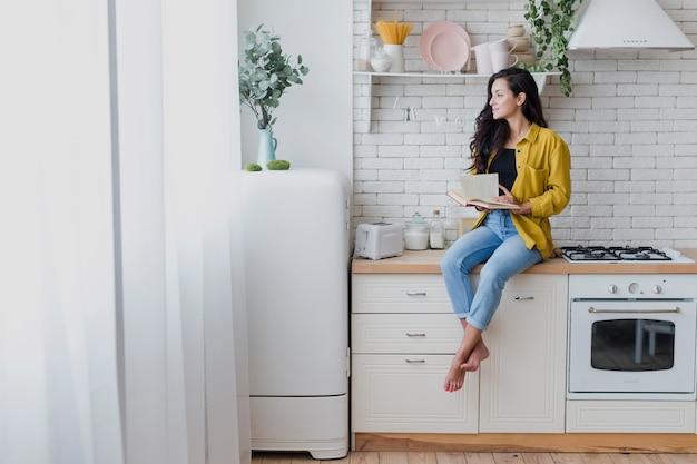 Mulher de tiro completo com livro na cozinha