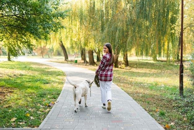 Mulher de tiro completo com melhor amigo no parque