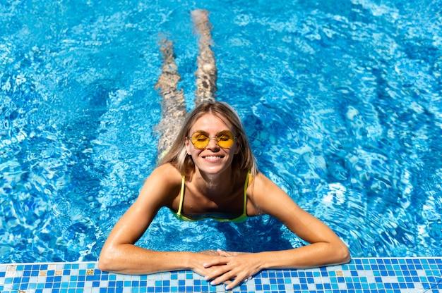 Mulher de tiro completo em ângulo alto de piscina
