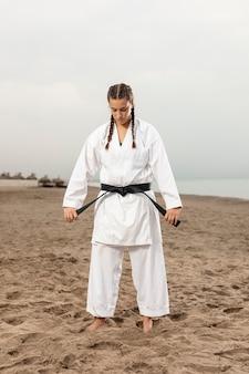 Mulher de tiro completo em roupa de artes marciais