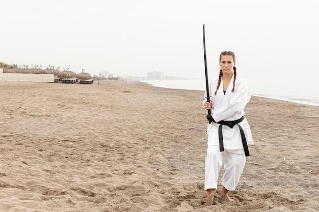 Mulher de tiro completo em traje de arte marcial ao ar livre