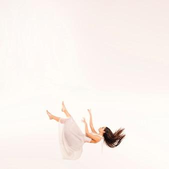 Mulher de tiro completo em vestido branco flutuante
