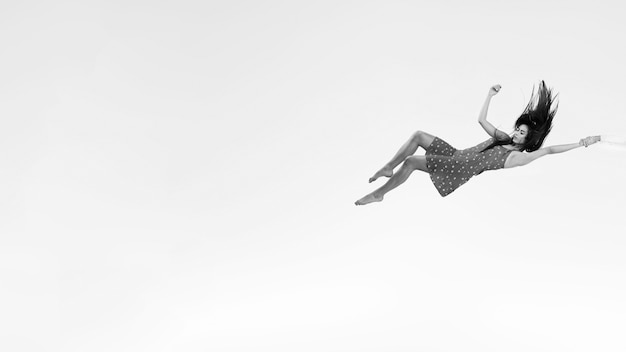 Mulher de tiro completo em vestido em tons de cinza flutuante