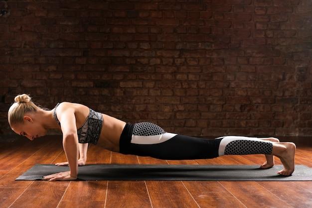 Mulher de tiro completo fazendo flexões