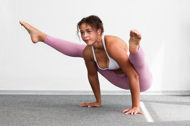 Mulher de tiro completo, mantendo as pernas esticadas