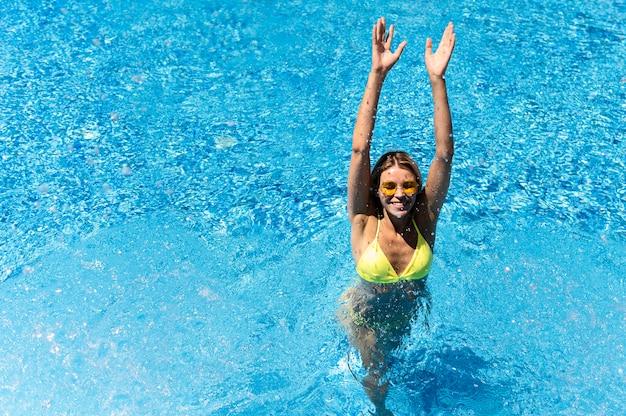 Mulher de tiro completo na piscina