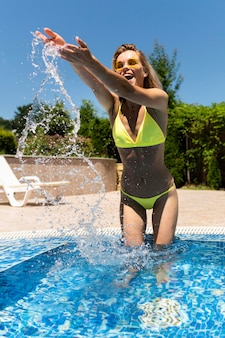 Mulher de tiro completo se divertindo na piscina
