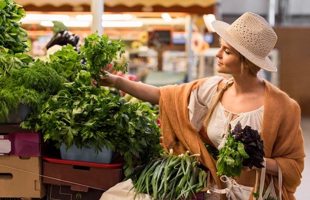 Mulher de tiro médio à procura de vegetais