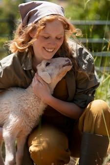 Mulher de tiro médio abraçando um cordeiro