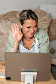 Mulher de tiro médio acenando para um tablet