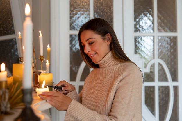 Mulher de tiro médio acendendo vela