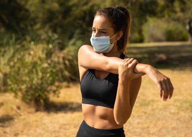 Mulher de tiro médio alongando-se com máscara