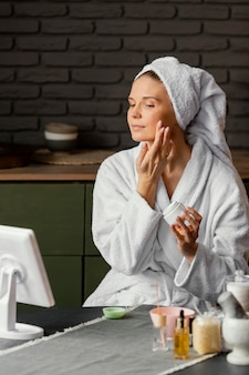 Mulher de tiro médio aplicando creme facial
