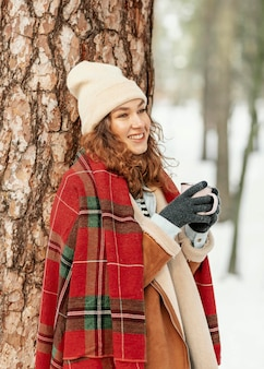 Mulher de tiro médio apoiado em uma árvore