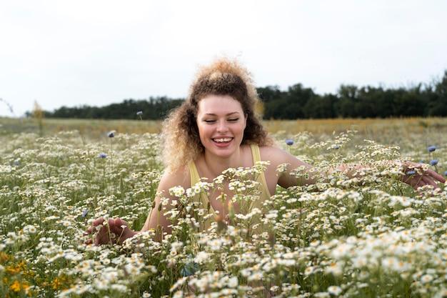 Mulher de tiro médio apreciando flores