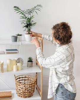 Mulher de tiro médio arrumando a planta