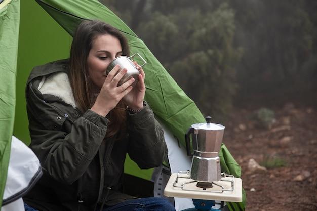 Mulher de tiro médio bebendo da caneca
