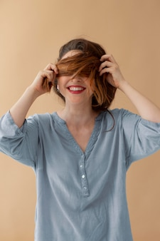 Mulher de tiro médio cobrindo os olhos com cabelo
