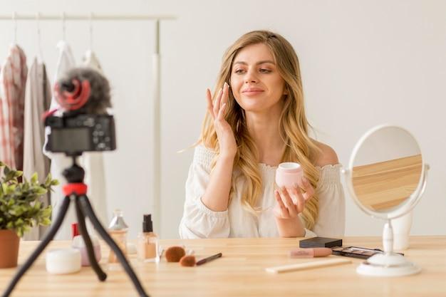 Mulher de tiro médio colocando maquiagem