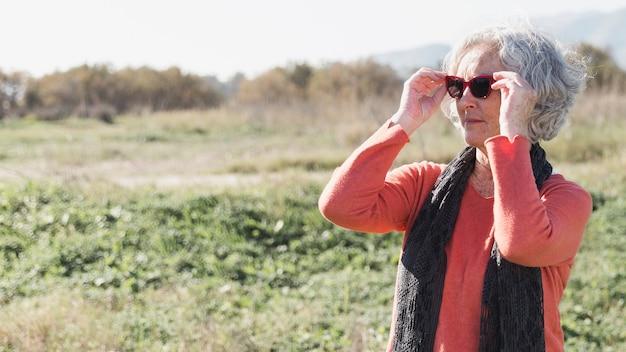 Mulher de tiro médio colocando óculos de sol
