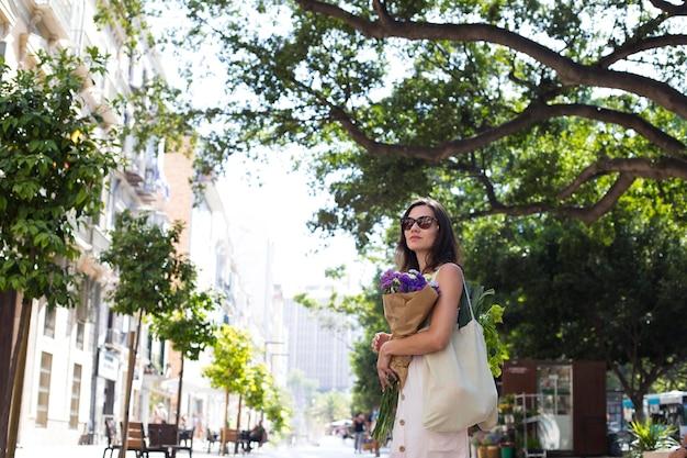 Mulher de tiro médio com bouquet floral