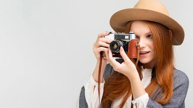 Mulher de tiro médio com câmera e chapéu