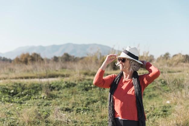 Mulher de tiro médio com chapéu e óculos de sol