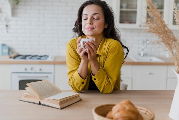 Mulher de tiro médio com copo e livro