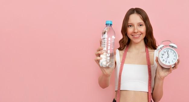 Mulher de tiro médio com garrafa e relógio