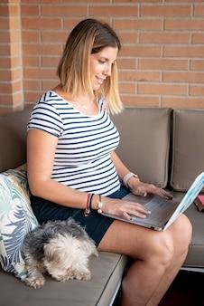 Mulher de tiro médio com laptop sentado no sofá