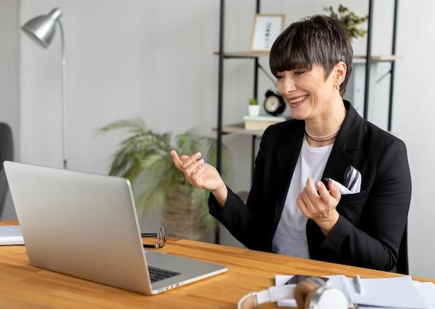 Mulher de tiro médio com laptop trabalhando