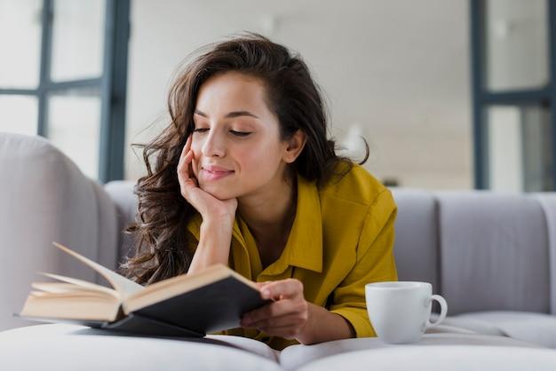 Mulher de tiro médio com livro e copo