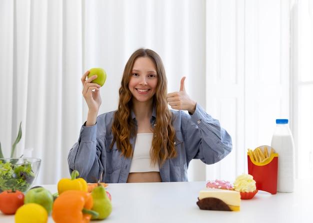 Mulher de tiro médio com maçã e polegar para cima