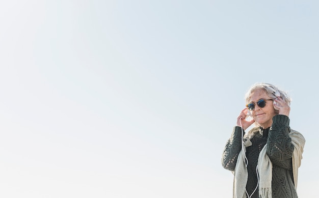 Mulher de tiro médio com óculos escuros e fones de ouvido