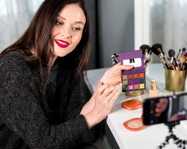 Mulher de tiro médio com paleta de maquiagem