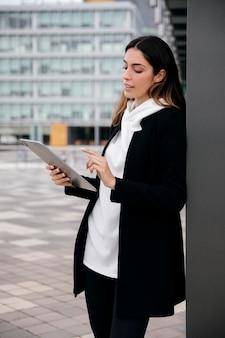 Mulher de tiro médio com tablet ao ar livre