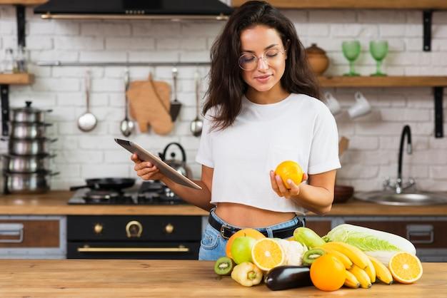 Mulher de tiro médio com tablet olhando uma laranja