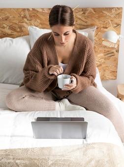 Mulher de tiro médio com xícara na cama