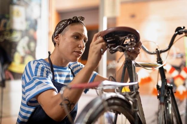 Mulher de tiro médio consertando bicicleta