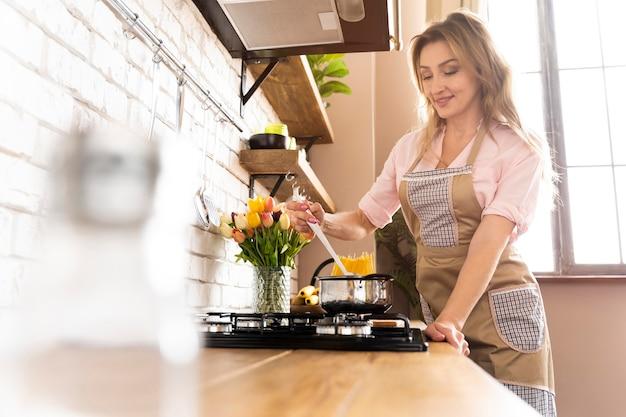 Mulher de tiro médio cozinhando no fogão Foto Premium