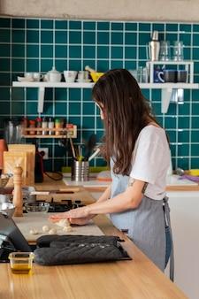 Mulher de tiro médio cozinhando