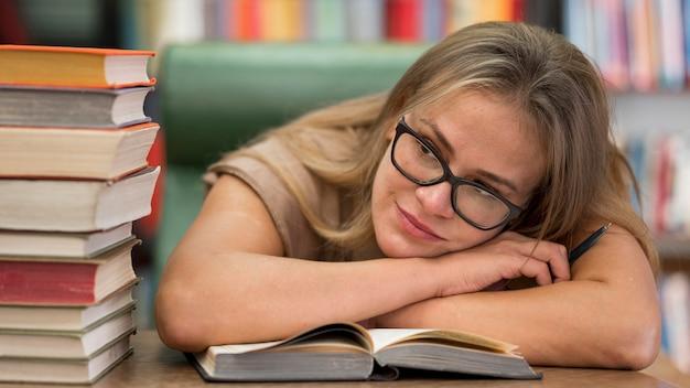 Mulher de tiro médio deitada em um livro