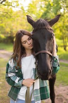 Mulher de tiro médio e cavalo na natureza